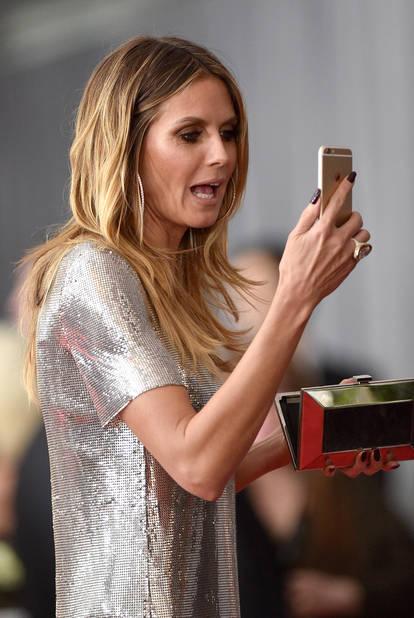 Dans le clutch d'Heidi Klum, son téléphone pour faire des photos... ou pour voir si elle n'a pas d'épinards dans les dents.