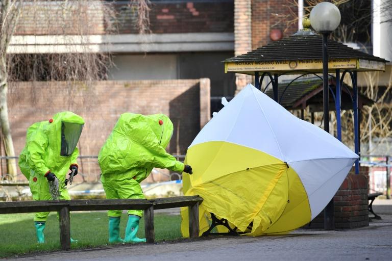 Des membres des services d'urgences en combinaison de protection installent une tente de protection sur le banc où un homme et une femme ont été trouvés dans un état critique quelques jours auparavant, le 8 mars 2018 à Salisbury, au Royaume-Uni