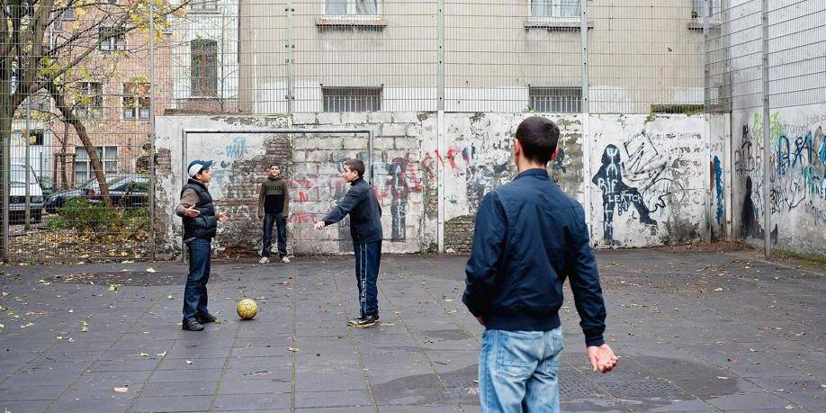 Brussels, Belgium, November 10, 2009 Moroccan boys play football on a fenced little square in the Anneessens quarter in the city centre. Reporters©Nick Hannes