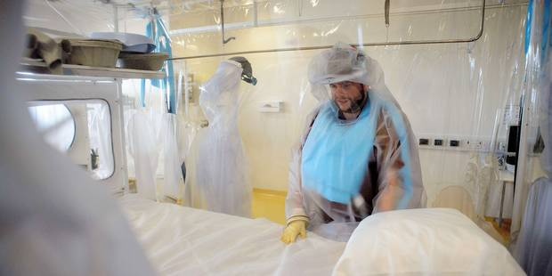 A nurse wears protective clothing as he demonstrates the facilities in place at the Royal Free Hospital in north London on August 6, 2014, in preparation for a patient testing positive for the Ebola virus. The specialised unit allows a team of doctors and nurses to provide care for anyone with the contagious condition. Despite it's high mortality level, Consultant Stephen Mepham advised against panic, stating that the chances of meeting an undiagnosed patient are virtually impossible with next to no chance of catching the virus without exposure to the sufferer's bodily fluids. AFP PHOTO/Leon Neal