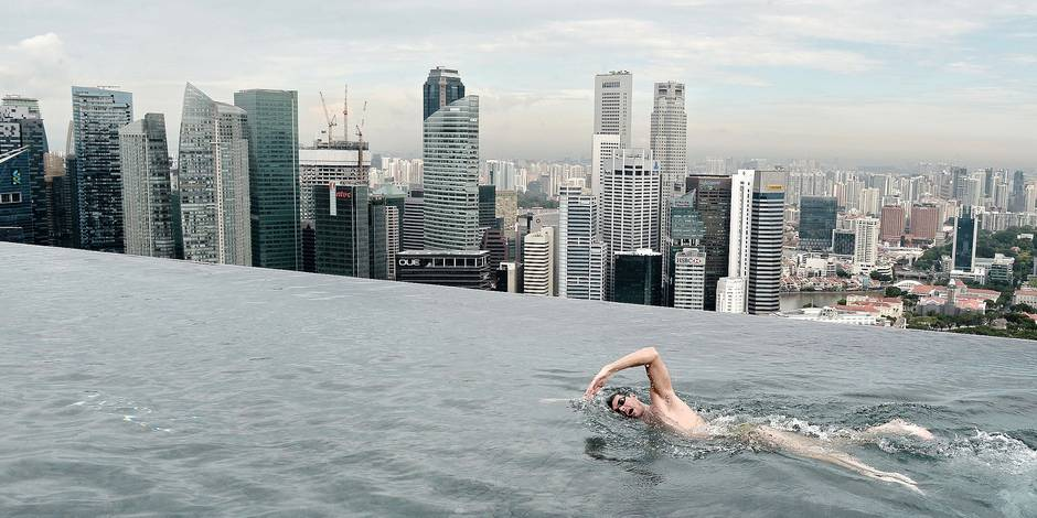 TOPSHOTS -- AFP PICTURES OF THE YEAR 2014 -- World Champion Christian Sprenger of Australia swims during a swimming clinic session for children with special needs on the rooftop pool of the Marina Bay Sands resort hotel in Singapore on May 20, 2014. Sprenger is in Singapore to promote the Singapore Swim Stars held in September, a three-day swim festival that includes an unprecedented competition format involving some of the world's best swimmers which will showcase a syncronised swimming as well as swimming clinics. AFP PHOTO/ROSLAN RAHMAN