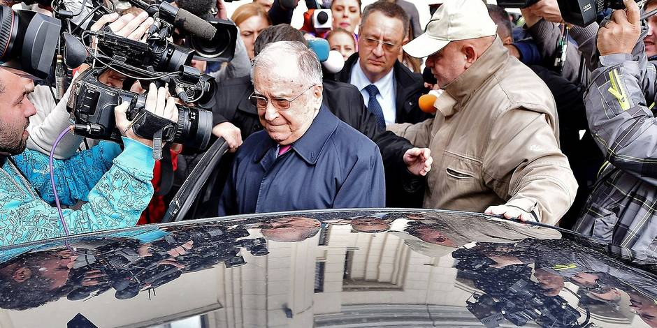 Ion Iliescu (C), former Romanian President leaves the court after he was interrogated by prosecutors in Bucharest on October 21, 2015. A Romanian court has launched a probe into former president Ion Iliescu for alleged crimes against humanity over the violent suppression of protests in 1990, months after the fall of the Communist regime, prosecutors said Wednesday. AFP PHOTO / GRIGORE POPESCU