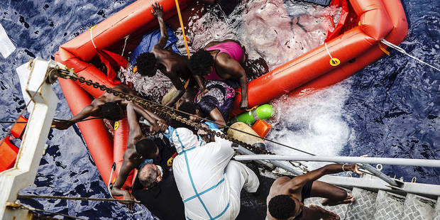 SICILIAN STRAIT, MEDITERRANEAN SEA - MAY 30: Refugees stands in a boat as ships of Italian Navy rescue refugees from an overcrowded boat which was about to capsize at Sicilian Strait, between Libya and Italy, in Mediterranean sea on May 30, 2016. Marina Militare / Anadolu Agency Reporters / Abaca
