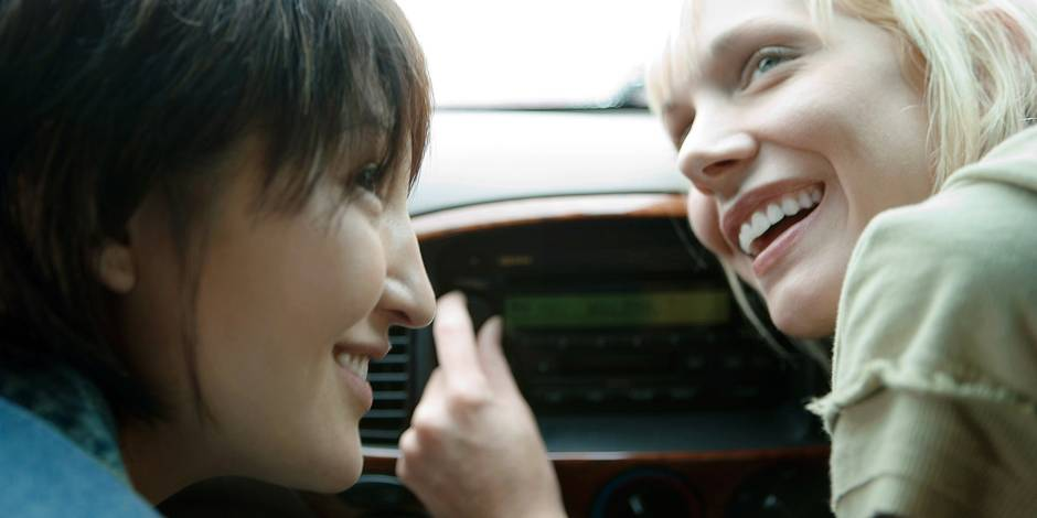 Two female friends in car, one tuning radio