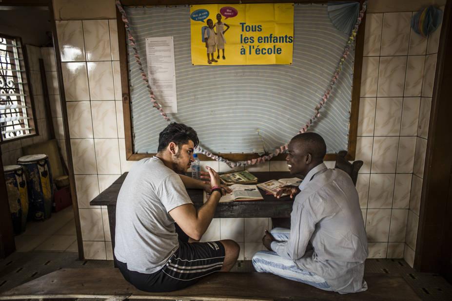 Bilal aide à la lecture au dessous d'une pancarte « tous les enfants à l'école ».