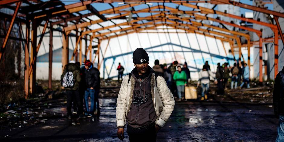 Migrants walk in an abandoned printing factory in the western Serbian town of Sid, on December 7, 2017. Exhausted as being stuck in Serbia for months, dozens of young migrants survive in appalling conditions in Sid, a small town bordering European Union, which they try to enter every day. As winter has came, every morning in freezing cold they go towards a closed printing factory, the last stop before Croatia. / AFP PHOTO / Andrej ISAKOVIC