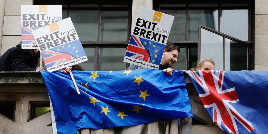 """People demonstrate against Brexit on a balcony in London Wednesday, Feb. 14, 2018, as Britain's Foreign Secretary Boris Johnson delivers a speech focusing on Britain leaving the EU. The Foreign Office says Johnson will use a speech Wednesday to argue for """"an outward-facing, liberal and global Britain"""" after the U.K. leaves the bloc. (AP Photo/Frank Augstein)"""